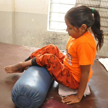 A child with spinal cord injury receiving therapy at APD India